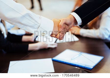 Business men hand shake. In the beautiful spacious audience