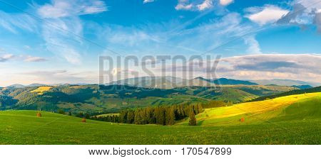 Panorama Carpathian mountain summer landscape with blue cloudy sky, beautiful sunbeam and agriculture fields. Ecological environment. Positive scene.