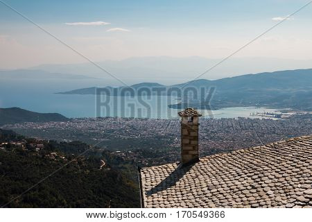 Scenic view from above a slate roof in a village up a mountain, down towards a bay