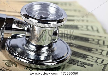 Macro photograph of stethoscope on American money.  Focus is on front edge of stethoscope.