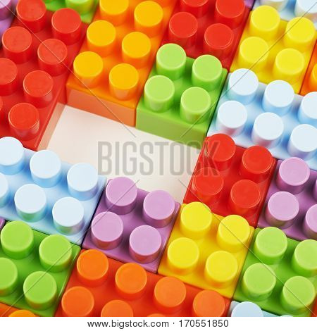 Surface covered with plastic and colorful construction toy bricks with a single one missing, framed as a backdrop composition