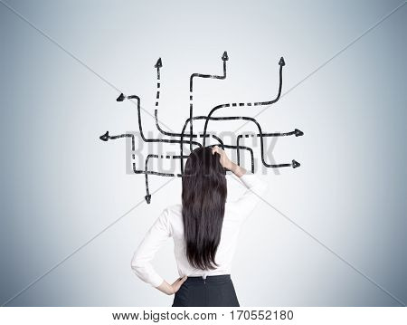 Woman Looking At Tangled Arrows On Gray Wall