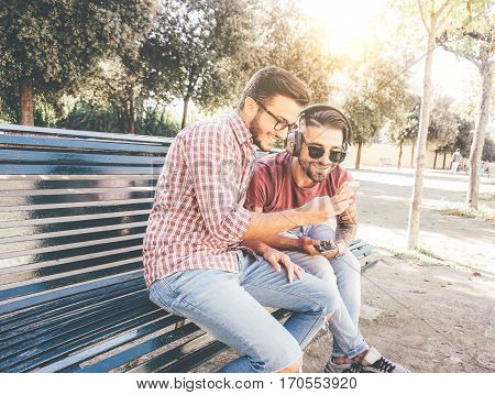 Two friends mates sitting on a bench in a park on a sunny day watching funny videos on social media with mobile smart phone - Two happy young men standing outdoor listening to music relaxing on bench