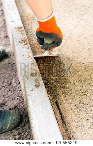 Worker with orange glove uses paving trowel to make smooth a sand foundation