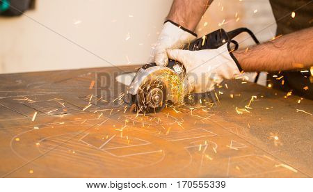 Craftman cutting iron with grinder and making sparks