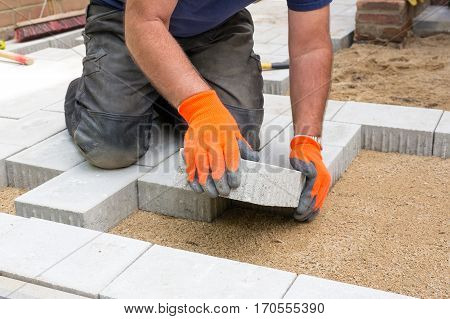 Hands of a builder laying new paving stones carefully placing one in position on a levelled and raked soil base