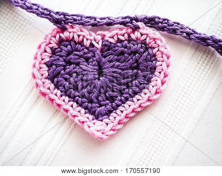 Closeup of purple crocheted heart with pink trim on a purple garland chain