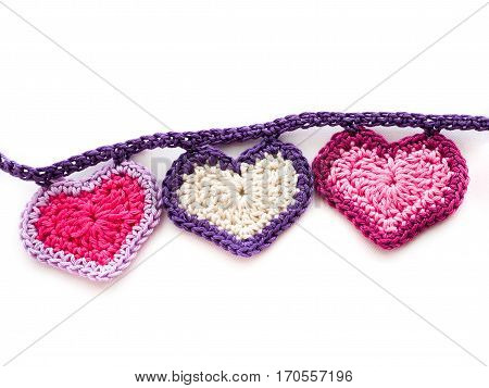 Three crocheted hearts with contrasting trim on a garland chain