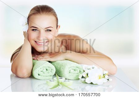 Portrait of a beautiful smiling woman lying down on massage table, happy and healthy vacation in the wellness hotel, enjoying pleasant procedure at spa salon