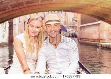 Happy couple in Venice, beautiful young people riding on the gondola along river on narrow street, romantic honeymoon in Italy, Europe