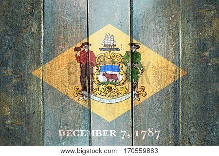 Vintage delaware flag on grunge wooden panel