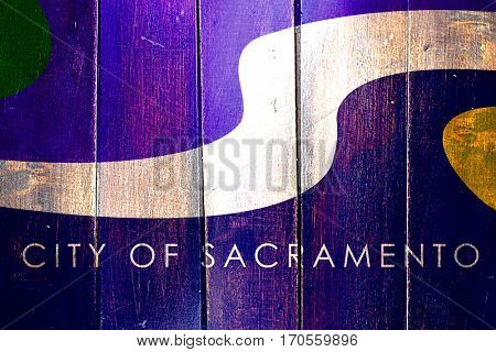 Vintage Sacramento flag on grunge wooden panel