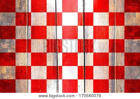 Vintage chequered golf or racing  flag on grunge wooden panel