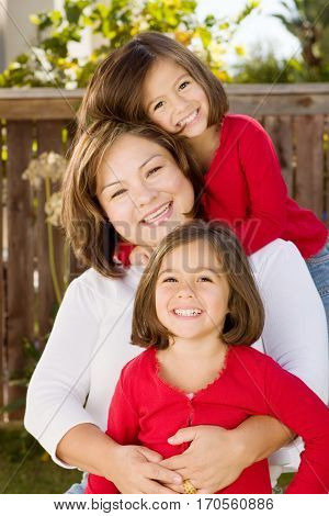 Portrait of a happy Hispanic mother hugging her daughters.