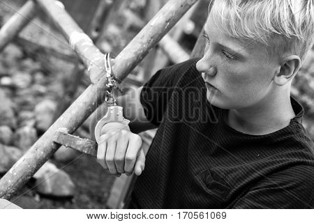 Remorseful Young Boy Handcuffed To A Metal Bar