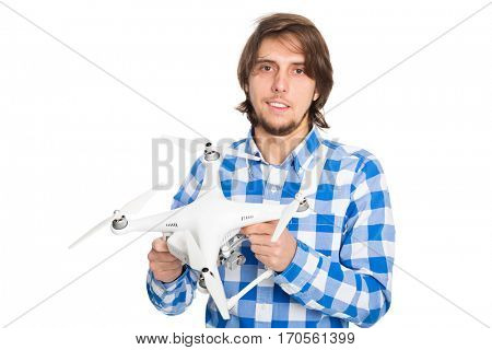Joyful man holding a flying copter with a camera. Isolated on white.