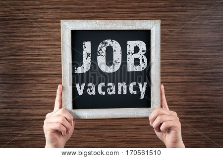 Labor market concept. Female hands holding chalkboard with text JOB VACANCY on wooden background