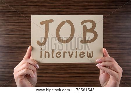 Labor market concept. Female hands holding paper with text JOB INTERVIEW on wooden background