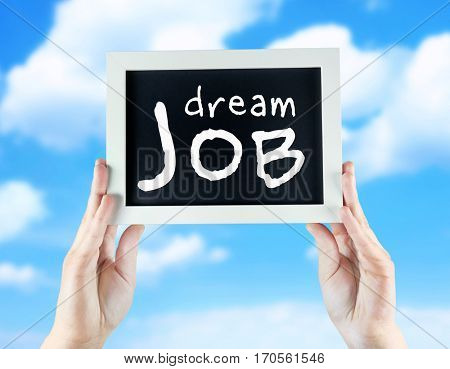 Labor market concept. Female hands holding chalkboard with text DREAM JOB on sky background