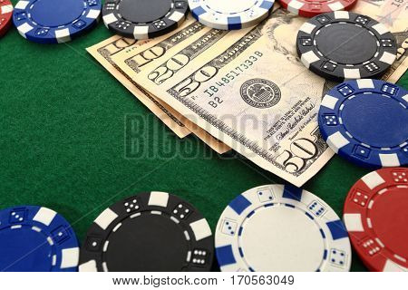 Poker chips and money close up. Dollars and chips on green casino table closeup. Casino games background.