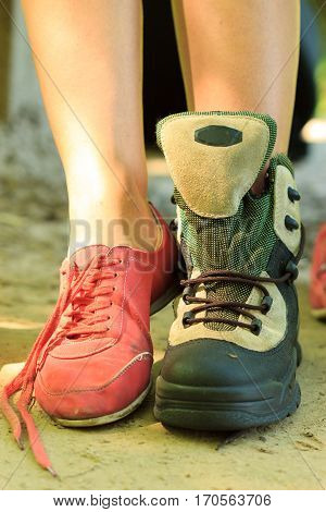 Holidays trip camping tourism relax trekking concept. Girl compare footwear. Hiking female examine her boots during break.
