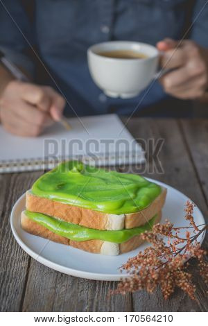 break time coffee time with pandan custard cream on toasted holding coffee cup and working for advertising or busy work concept