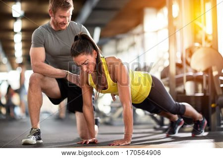 Tired sportswoman doing pushups with instructor's assisting