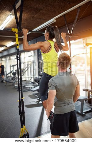 Woman trained on exercise equipment with coach in gym- back view