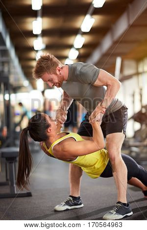 Couple enjoying in exercising together in gym