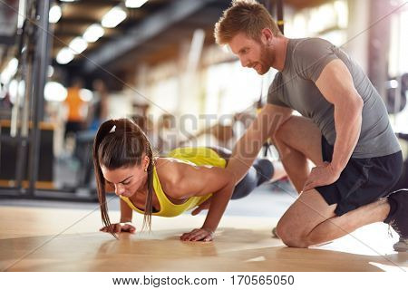 Sportswoman train with coaches help in gym