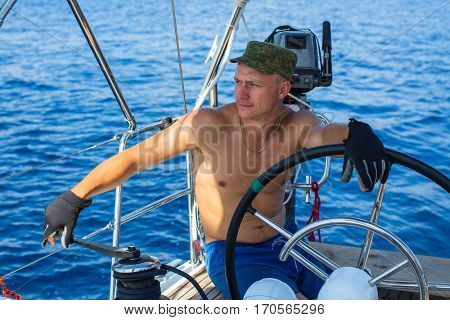 Young man skipper of a sailing yacht. Luxury vacation. Extreme sports.