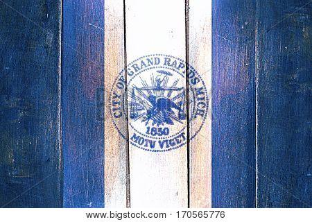 Vintage Grand rapids flag on grunge wooden panel