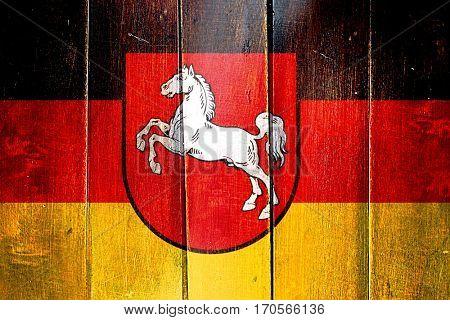 Vintage lower saxony, niedersachsen flag on grunge wooden panel