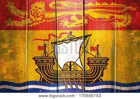Vintage New brunswick flag on grunge wooden panel