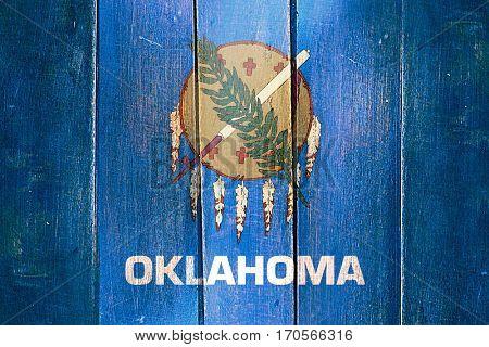 Vintage oklahoma flag on grunge wooden panel