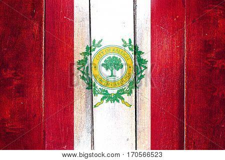 Vintage Raleigh flag on grunge wooden panel