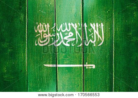 Vintage Saudi Arabia  flag on grunge wooden panel
