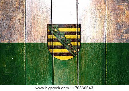 Vintage Saxony, sachsen flag on grunge wooden panel