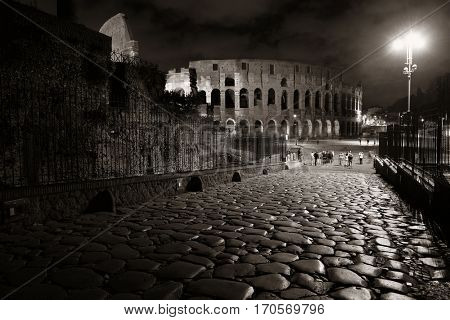 Colosseum at night with stone pattern street, the world known landmark and the symbol of Rome, Italy.