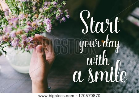 Life quote. Motivation quote on soft background. The hand touching purple flowers. Start your day with a smile.