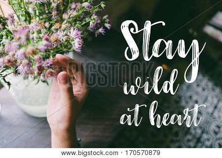 Life quote. Motivation quote on soft background. The hand touching purple flowers. Stay wild at heart