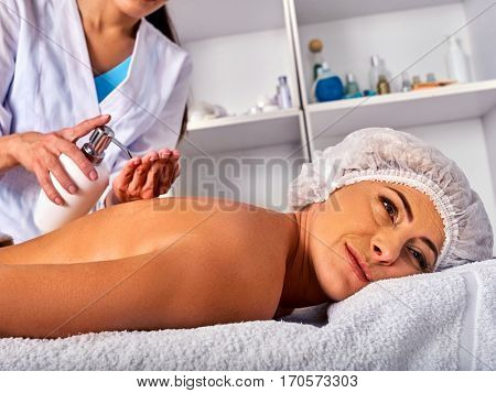 Massage woman therapist making manual therapy back. Hands of masseuse close up. Treatment of spinal injuries 40 old client in spa salon. Beautician uses natural cosmetics.