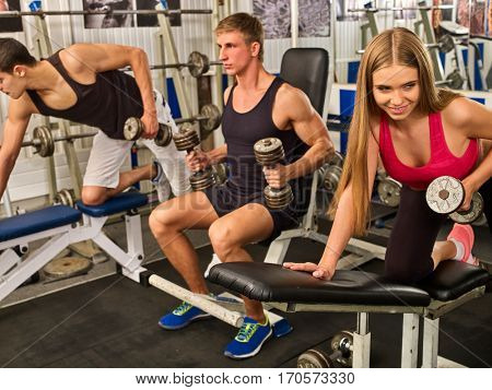 Friends in gym together workout with fitness equipment. Man holding dumbbell workout at gym. Group people working strong muscular on simulator his body . Smiling woman on foreground.