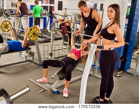 Fitness friends workout gym. Woman working on bench press. She lifting barbell. Man backs girl while taking exercises. Group work people on treadmill background.