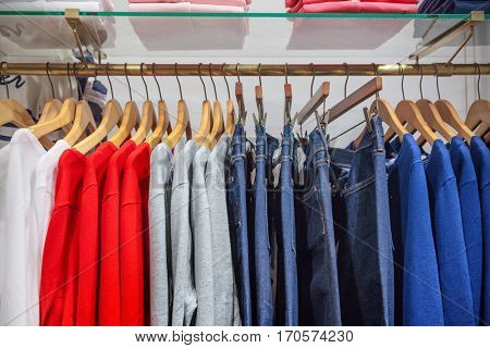 A row of clothes hanging on the rack.