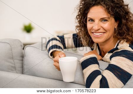 Beautiful woman sitting on the sofa and drinking a coffee