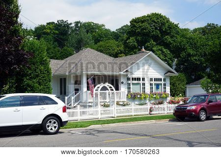 HARBOR SPRINGS, MICHIGAN / UNITED STATES - AUGUST 4, 2016: A Harbor Springs home with a white picket fence, on Third Street in Harbor Springs, flies the American Flag.