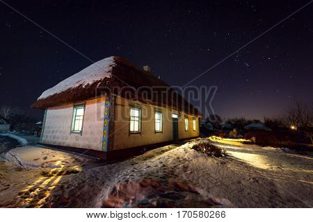night scene with old house with thatch roof