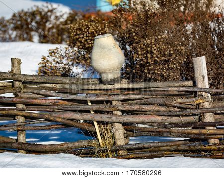 clay jug on wooden fence in sunny winter day
