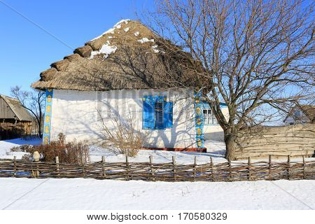traditional ukrainian house with thatch roof in sunny winter day